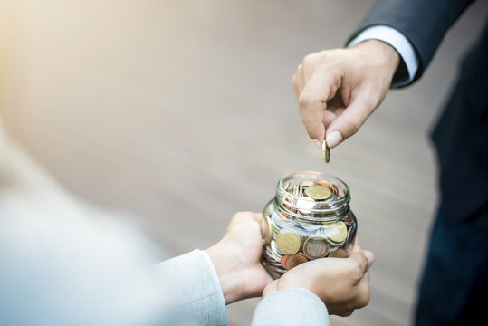Businessman hand putting money (coin) in the glass jar held by a woman