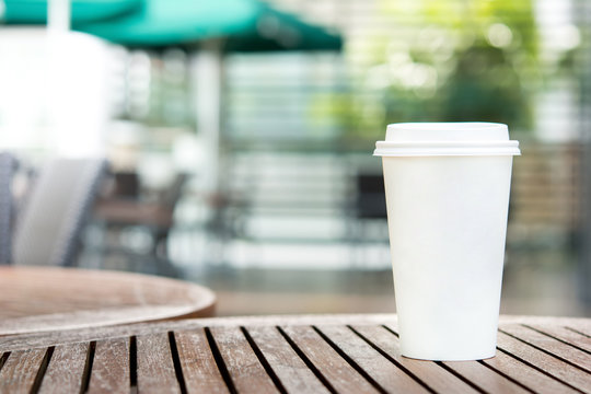 White paper coffee cup on wood table in outdoor cafe