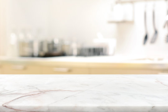 Marble stone table top (kitchen island) on blur kitchen interior background