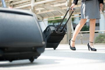 Businesswoman (lower part) walking and pulling luggage