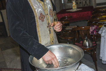 The priest assistant filled Christening Baptismal Font with Holy Water at the church during the ceremony