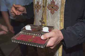 The priest holds church utensils, glans, ceremony of water baptism, various objects needed for baptism christening