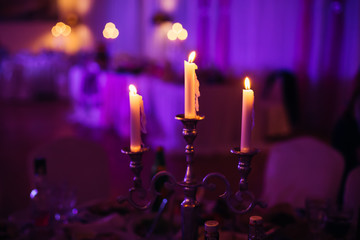 Lighted candles stand on the festive served dinner table in purple light