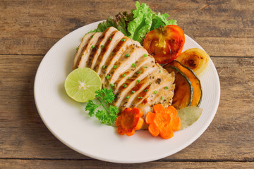 Sliced chicken breast barbecue on white plate served with grilled vegetable. Delicious  chicken breast steak and salad for dinner. Homemade chicken breast barbecue on wood table for background.