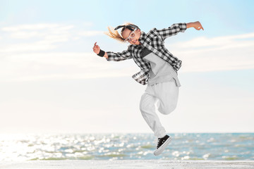 Fashion child dancing over sky background.