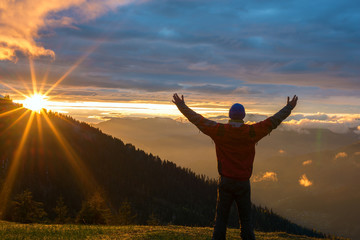 Man traveler with open arms admires a colorful sunset in the mountains