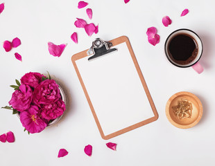 Clipboard with empty paper, coffee and pink roses, top view