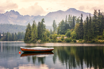 Beautiful alpine lake surrounded by rocky mountains with boat and green fir trees, popular tourist destination, lake Strbske pleso, High Tatras, Slovakia (Slovensko)