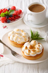 Lemon tart with meringue and coffee with milk close-up. vertical