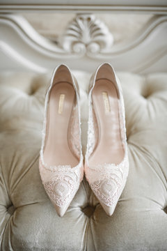 Bride's shoes with laces stand on white sofa