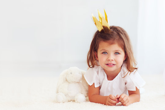 portrait of cute little baby girl laying on carpet with toy bunny
