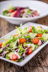 Vegetable salad. Plate of salad with vegetables  on rustic oak table. Assortment of ingredients of vegetable salad.