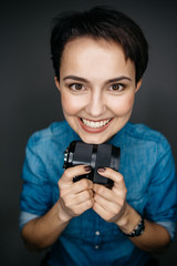 Cheerful girl photographer holding a photo lens in her hands, smiling. Studio shot isolated on gray