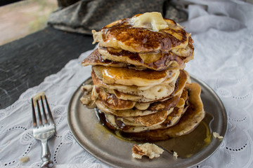Sloppy stack of pancakes with butter and syrup