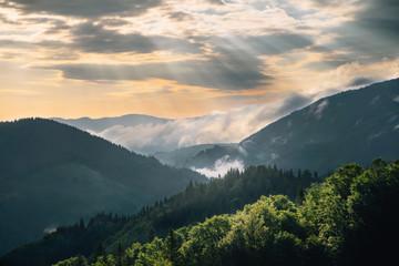 Photo sur Aluminium Colline Mountain hill with fog and sunbeam at sunrise