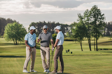 Multiethnic group of golfers holding clubs and talking while standing on green grass