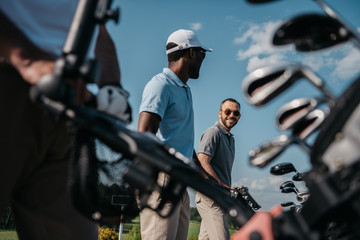 smiling players going to the golf course, bag with clubs at foreground