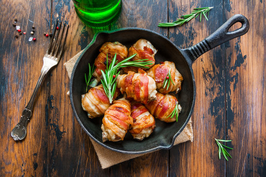 Oven roasted bacon wrapped chicken drumsticks in a black baking pan on the wooden rustic table, top view.