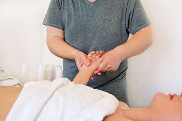 Hand massage in massage relax studio. A physiotherapist massaging palm and hand of a woman. Intensive relaxing full body massage, beating of woman fingers. Beauty, health care, medicine concept.