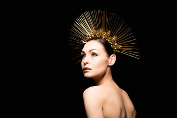 stylish naked lady in golden headpiece looking away isolated on black