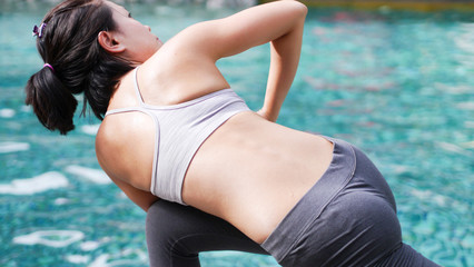 Professional asian woman practice yoga sequence Revolved Side Angle Pose (Parivrtta Parsvakonasana) close up back portrait beside swimming pool blue water
