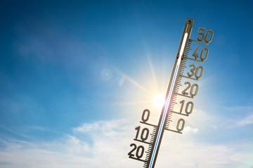 Thermometer mit strahlender Sonne und blauem Himmel im Hintergrund