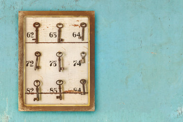 Small vintage cabinet with rusted hotel keys and room numbers