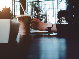 Start a good day and great work with iced coffee at a coffee shop in the morning. The image of a businessman at a coffee shop in the morning.