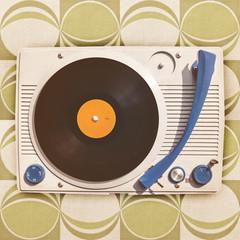 Vintage vinyl turntable player on retro wallpaper