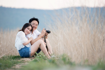 Beautiful young dating couple in city taking photos on park during sunset time