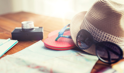 close up of travel map, flip-flops, hat and camera