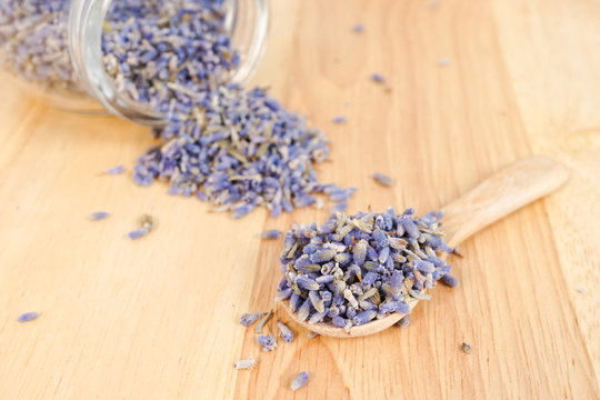 dried lavender flowers. a spoon full of lavender seeds on wooden background. shallow depth of field. Lavender scent is known for relaxation and a deep sleep.