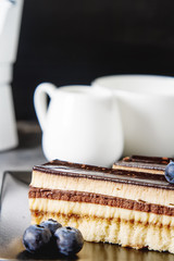 Delicious chocolate cake with blueberries and coffee. Dark backg