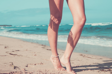 Tanned sexy legs of a woman against the sea, tropical beach scene, Bali island.