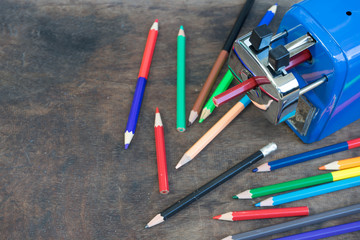 Color Pencils with sharpener on the wood table