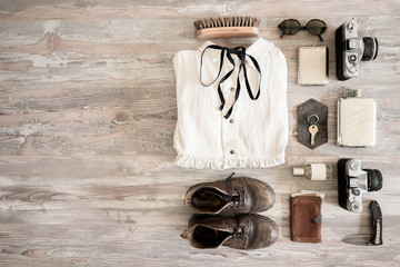 Preparation for traveling concept, dress, old shoes, jeans, beige hat, vintage cameras, leather bag, sunglasses, wallet, woman bra and another stuff on a white wooden background.