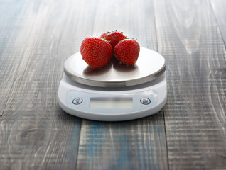 Three ripe washed strawberries lie on digital kitchen scales