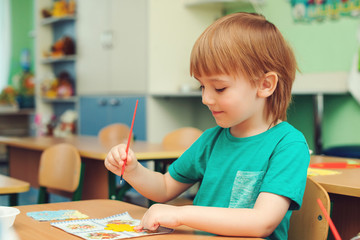 Cute little boy engaged in art and craft in classroom .