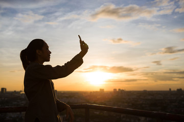 Silhouette of a girl that selfies in the city background when sunset time