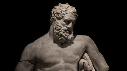 Statue of powerful Hercules, closeup, isolated at black background