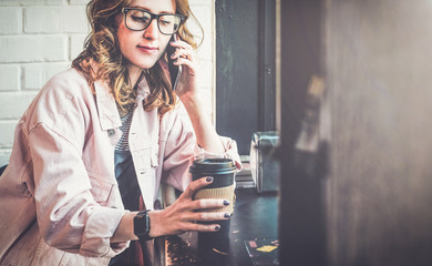 Hipster girl wearing glasses and a pink denim jacket sitting in a coffee house, drinking coffee and talking on cell phone.