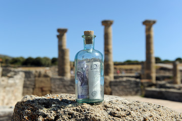 Billete de veinte libras esterlinas en unas ruinas romanas, conceptp del negocio del turismo