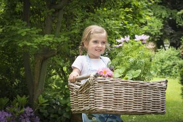 Girl gardening, carrying flowers in basket