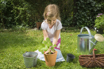 Little girl gardening, potting a plant