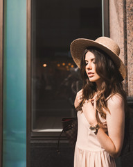 Close-up portrait of a slender young girl blogger beautiful brunette in downtown dusseldorf in a pastel dress and a lady's hat wearing sunglasses walking poses and smiling on the sunset