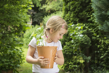 Little girl gardening, holding potted plant in hands
