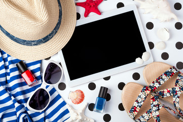 Summer women's accessories: sunglasses, hat, cosmetics, sandals, shirt and tablet on creative background. Vocations, travel and freelance work concept