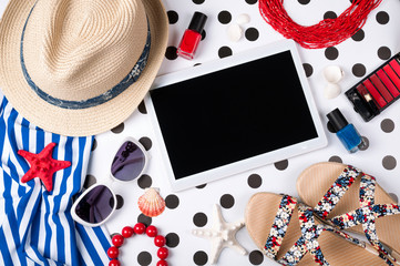 Summer women's accessories: sunglasses, hat, jewelry, cosmetics, sandals, shirt and tablet on creative background. Vocations, travel and freelance work concept. Top view