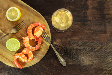 Glass of white wine with cooked shrimps and copyspace