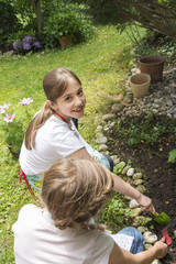 Two girls gardening, planting flowers together